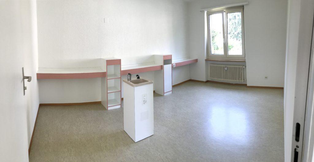 Bild eines Raums der gemietet werden kann. Man sieht ein Lavabo un ein Fenster.